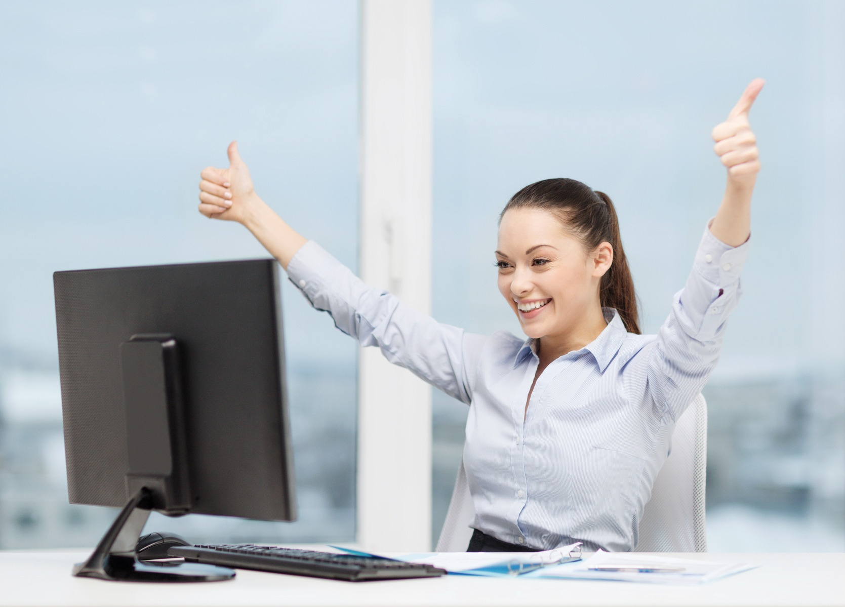 woman-with-computer-papers-showing-thumbs-up-m.jpg